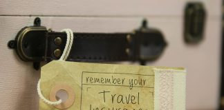 Paper tag with the handwritten words 'remember your travel insurance' on vintage suitcase