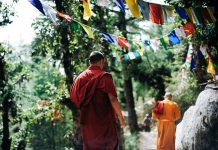 Two monks walking up a hilly terrain