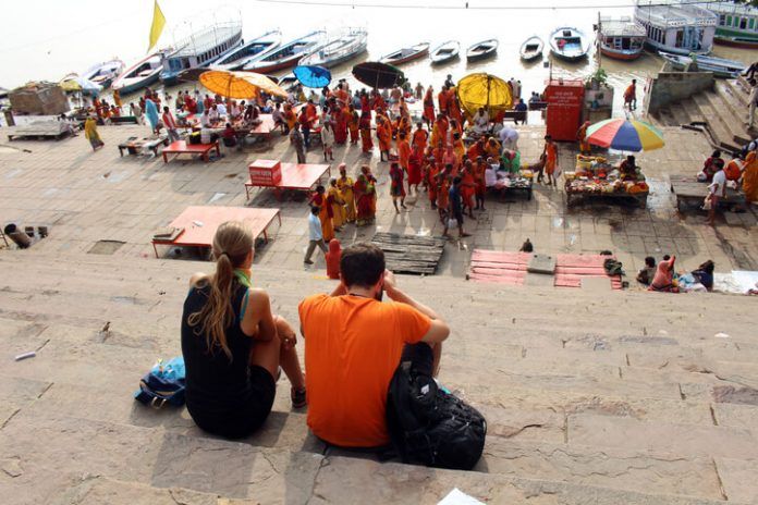 Tourists viewing the locals' ceremonies at Assi Ghat in Varanasi
