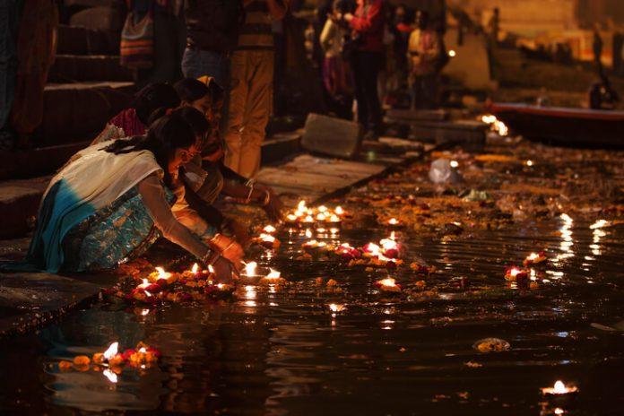 Locals leaving flowers and lit diyas into the Ganges at Manikarnika Ghat, Varanasi