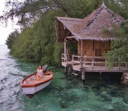 Woman sitting on a boat on the waters of Tiger Island (Palau Macan)