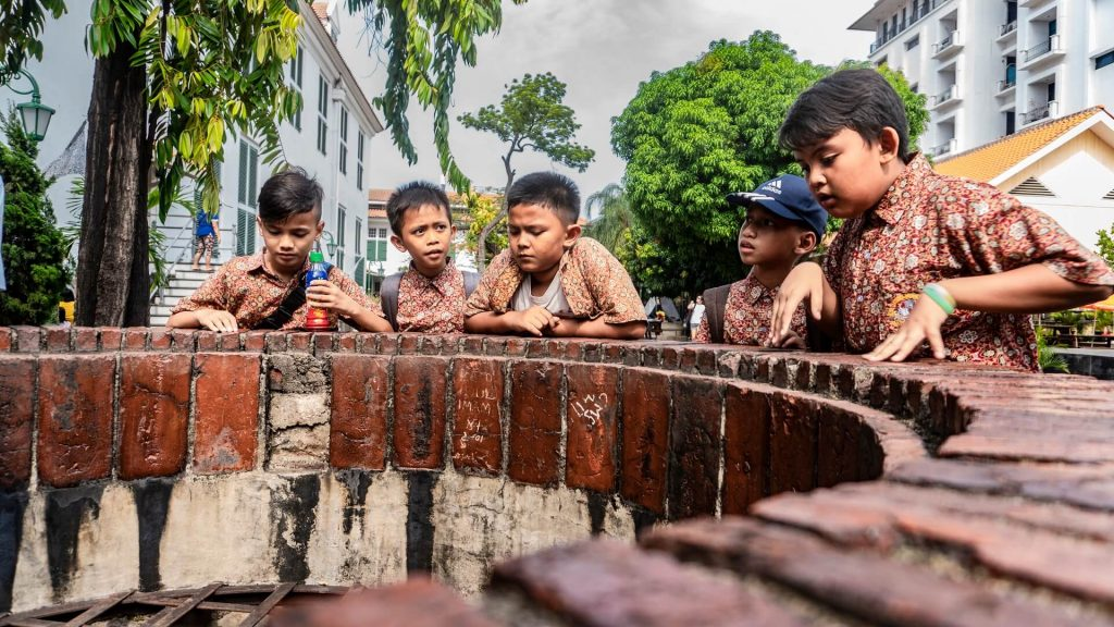Small boys standing around a well in Kota Tua, Jakarta, Indonesia