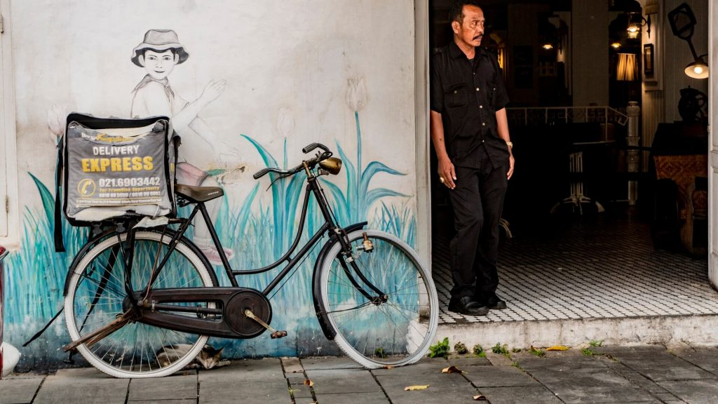 Man standing in a doorway beside a bicycle in Kota Tua, Jakarta