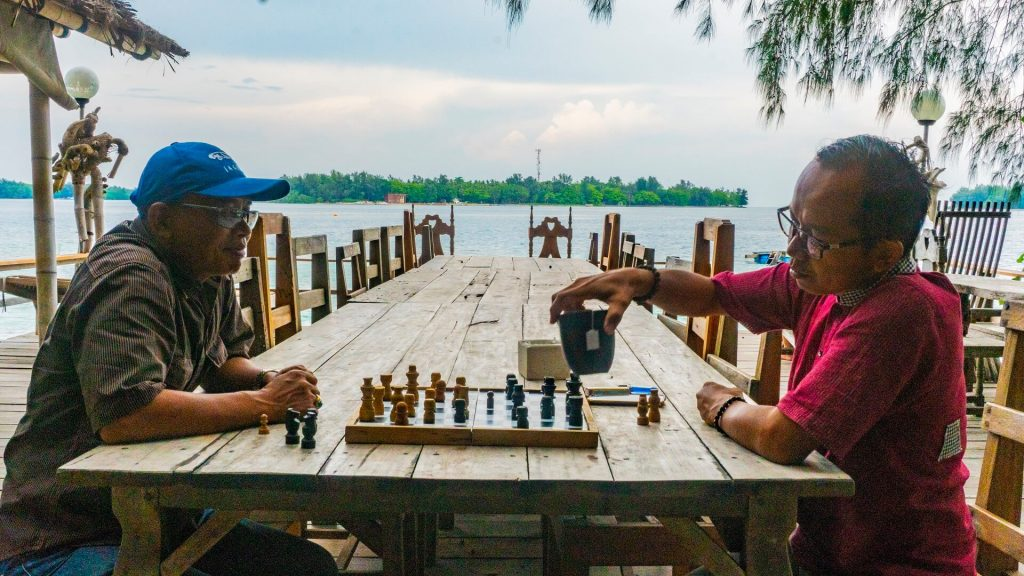 Men playing chess on Pulau Macan Island (Tiger Island)