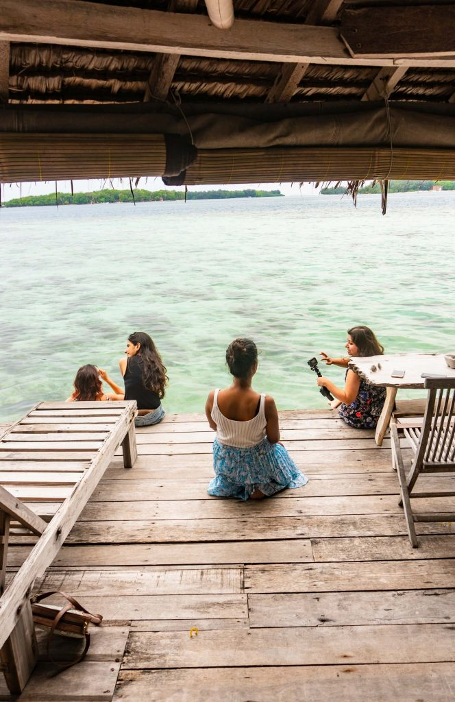 People sitting on the deck of Pulau Macan Island (Tiger Island)