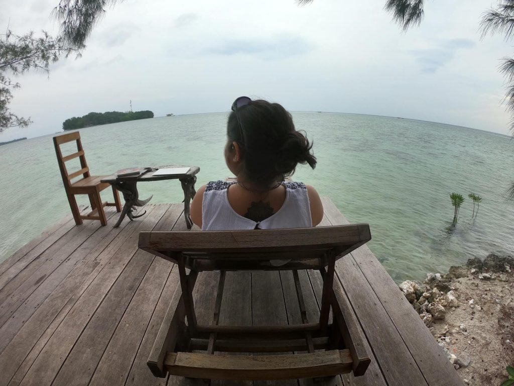 Woman sitting on a deck chair in Pulau Macan (Tiger Island)