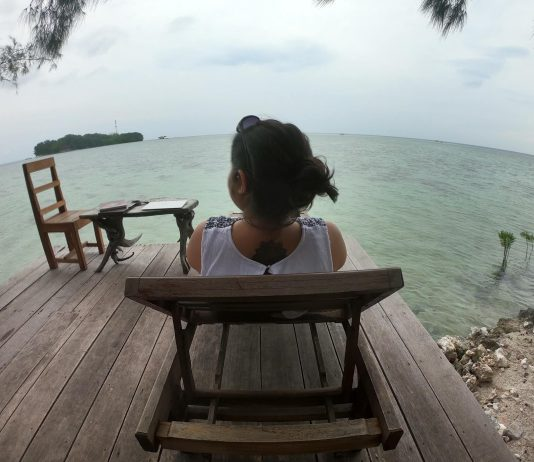 Woman sitting on a deck chair in Pulau Macan (Tiger Island)