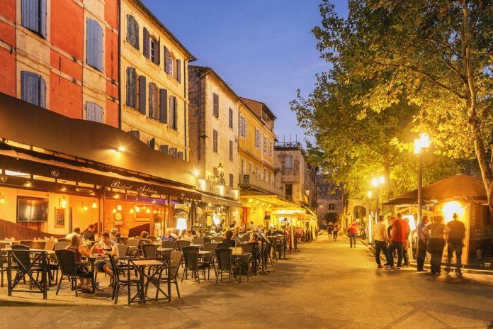 Arles, France - September 4, 2017: Locals and tourists spending time at the Place du Forum with its Cafés and Bistros.