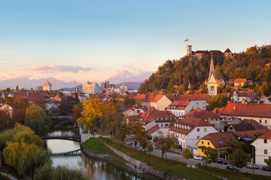 Cityscape of the Slovenian capital Ljubljana at sunset. Ljubljana castle on hill above town. River Ljubljanica running trough city center. Karavanke mountains in background, Yugoslavia