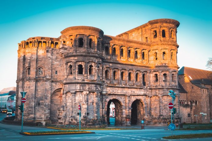 Classic view of famous Porta Nigra, the largest Roman city gate monument north of the Alps, in beautiful golden morning light at sunrise in summer, Rheinland-Pfalz, Germany