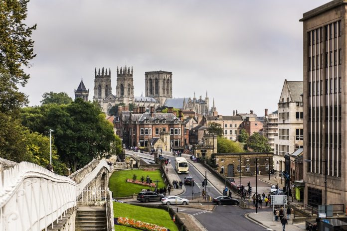 York, UK - September 27, 2015: Tourists walking along the old roman city walls of York with the York Minster in the background. The walls of York are the most complete example of medieval walls still standing in England.