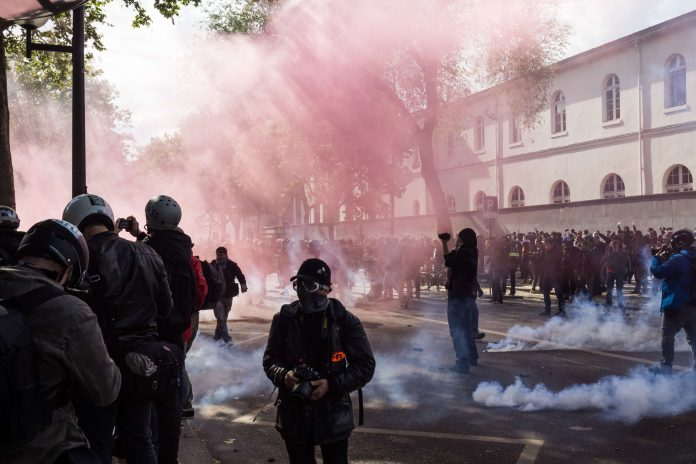 A pink smoke bomb and tears gas during the protest of may 1st 2017, in Paris. A lot of protesters and journalists. | Source: Unsplash