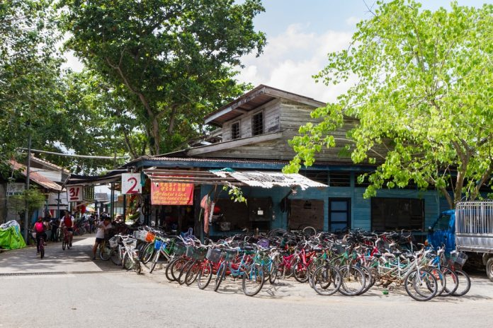 PULAU UBIN, SINGAPORE -March 11, 2016: Tourists ride past a shop with many bicycles for hire. Biking is the main mode of transportation on the island.