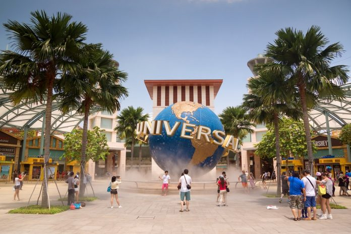 Visitors pose for photos with a revolving Universal Studios globe, outside the entrance to the Universal Studios Singapore theme park at Resorts World Sentosa. Singapore