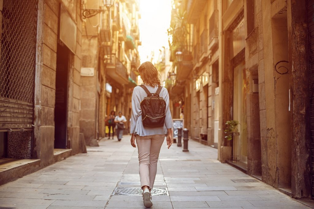 Traveling female walking on European city street, tourism in Europe, travel background