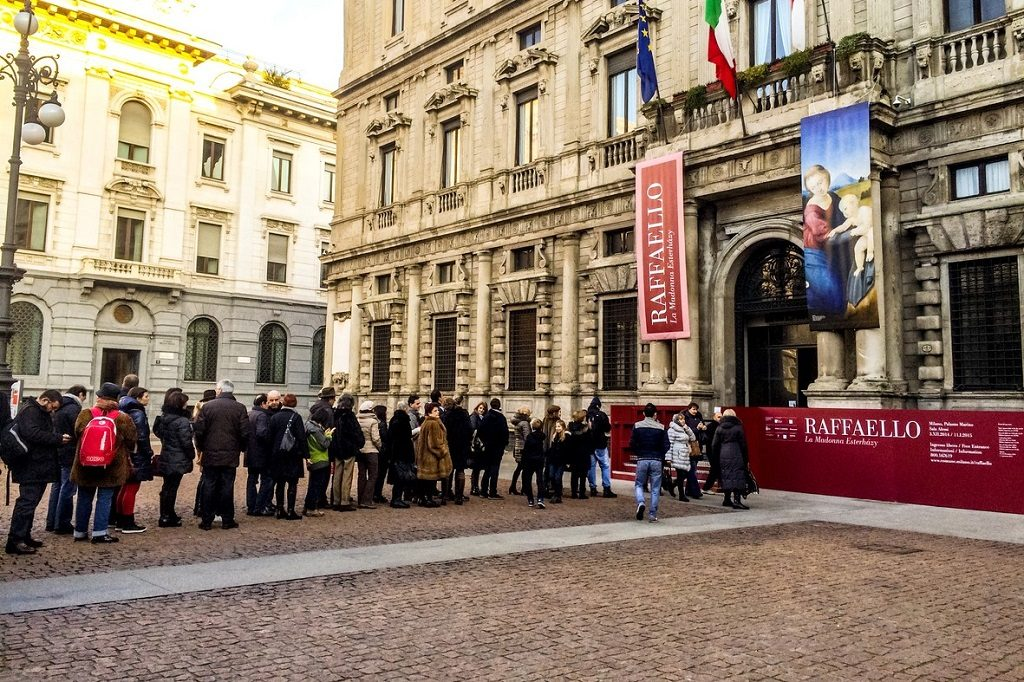 Milan, Italy - December 25, 2014: People waiting in line to enter temporary Raffaello Exhibit, Milan