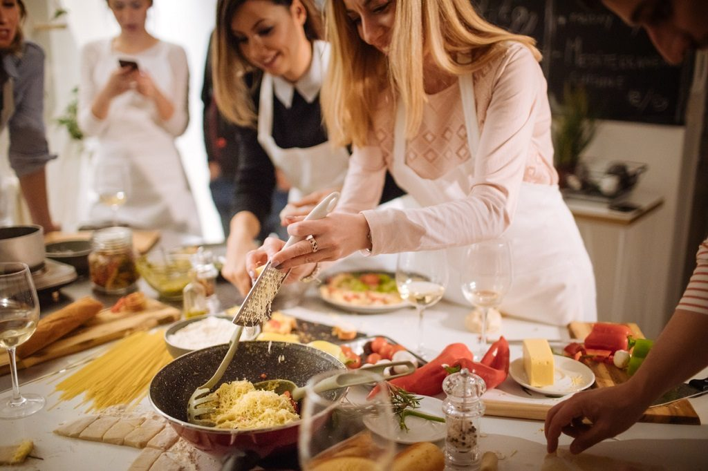 Photo of students in a kitchen preparing delicious pasta during a cooking class