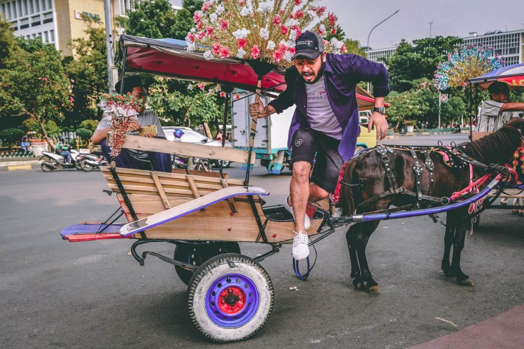 Man getting off a horse cart in Jakarta