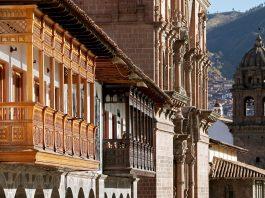 Balconies of colonial buildings with Iglesia La Compania de Jesus (Company of Jesus Church) in background.