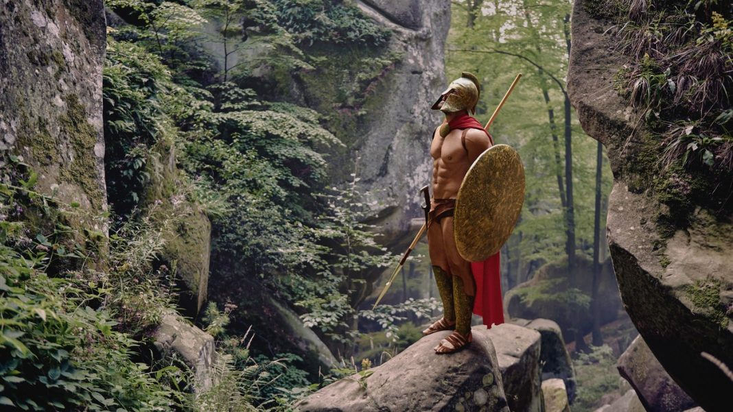 Full length shot of a Spartan soldier with perfect strong muscular body standing on a rock in the woods.