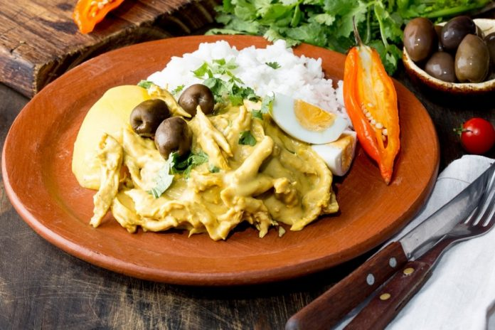MEXICAN AND PERUVIAN CUISINE. Aji de gallina. Chicken aji de gallina with olives egg and rice on clay plate. Tipical peruvian and mexican dish.