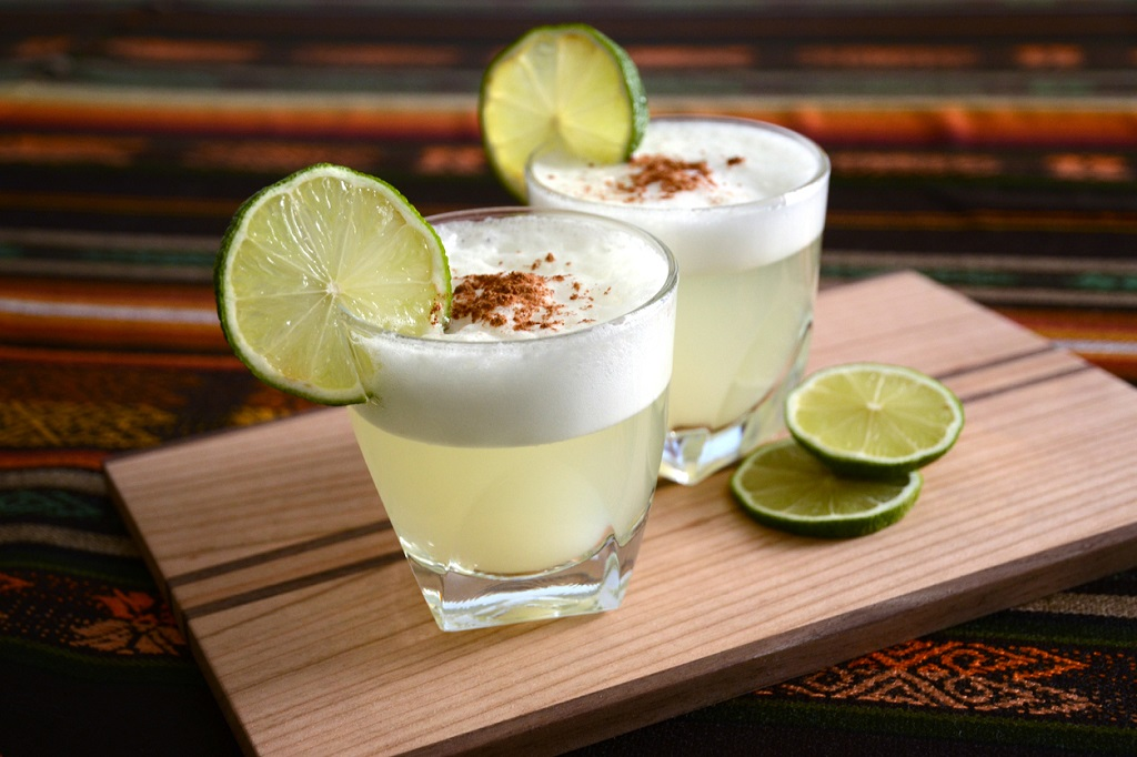 Two Pisco Sour cocktails standing on a table in a Peruvian restaurant with handmade tablecloth