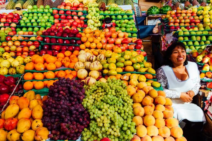 Arequipa, Peru - February 3, 2018: Daily Image. A saleswoman is sitting at her fruit stand in the San Camilo market in the morning of Arequipa. Local people frequent the market daily to buy groceries, fabrics or food