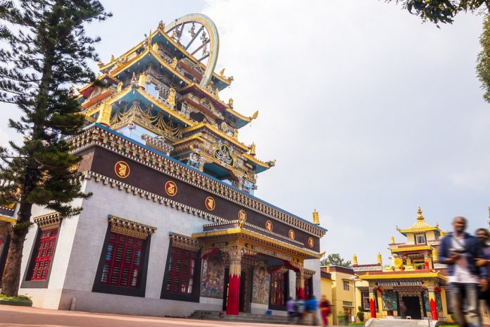 Bylakuppe, Karnataka, India - January 9, 2015: Entrance temple building and small meditation temple behind on the territory of the Namdroling Nyingmapa Monastery with moving in and out visitors.