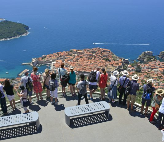 Dubrovnik, Croatia - June 20th 2016. Tourists view the historic city of Dubrovnik from the viewing platform by the cable car on the hill above the city. The island of Lokrum can be seen in the distance.