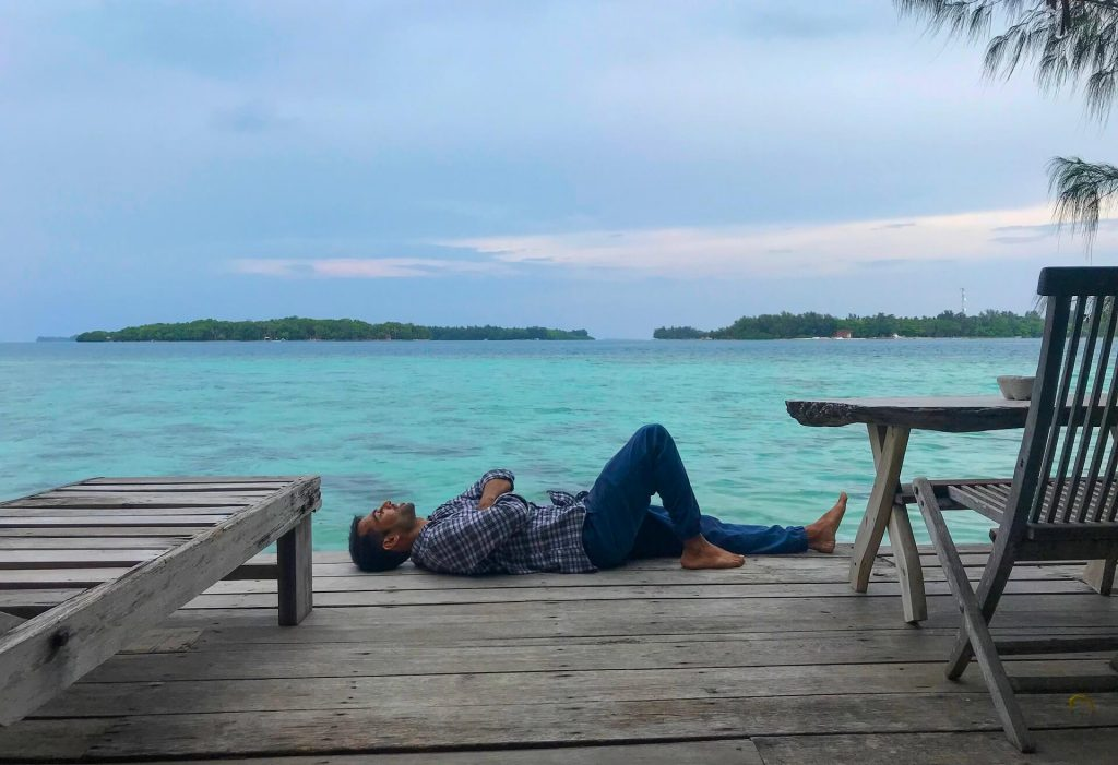 Man resting on a deck of Pulau Macan Island - Islands in Indonesia