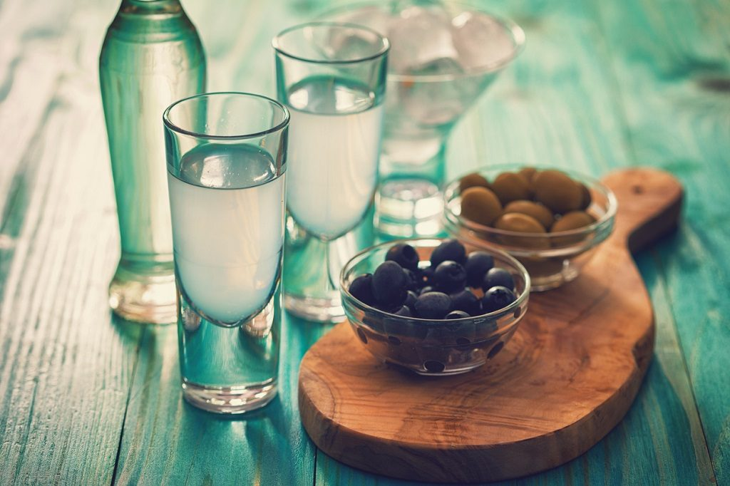 Favorite Greek summer drink Ouzo,flavor liquor made with the anise plant , served with Calamata Olives.