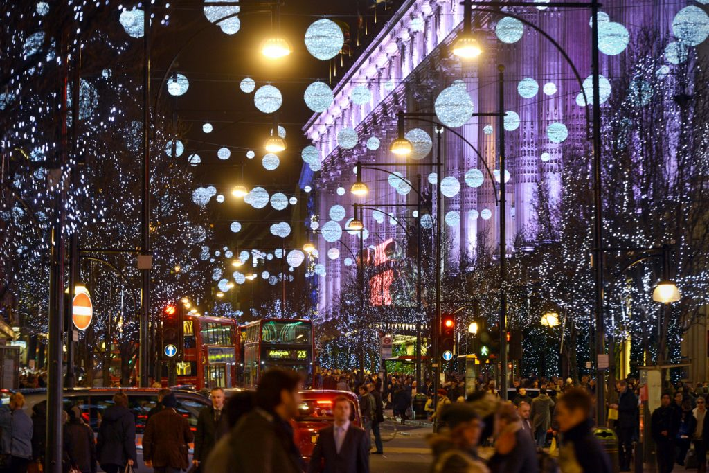 Christmas shoppers amongst the lights and traffic of Oxford Street in London's main retail district