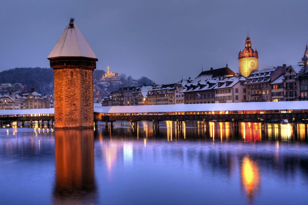 Winter-night composition of Lucerne/Luzern (Switzerland) skyline seen from Seebrucke, with the famous Chapel Bridge, the City-Hall Tower and Lucerne waterfront. On a hill in the foreground Chateau de Guetsch is visible. Winter, overcast evening