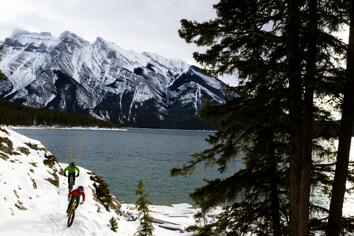 A man and woman enjoy a winter fat bike ride in the Rocky Mountains of Canada.