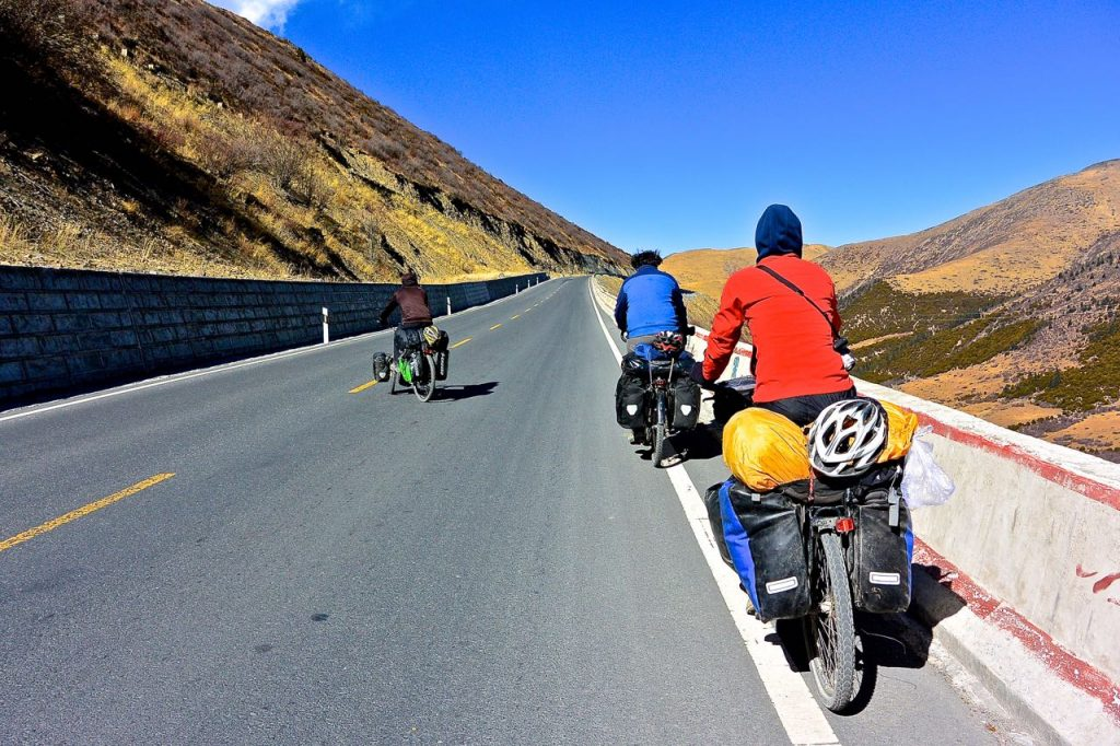 3 cyclists on the barren plateau of Tibet