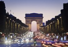Pretty night time illuminations of the Impressive Arc de Triomphe (1833) along the famous tree lined Avenue des Champs-Elysees in Paris.