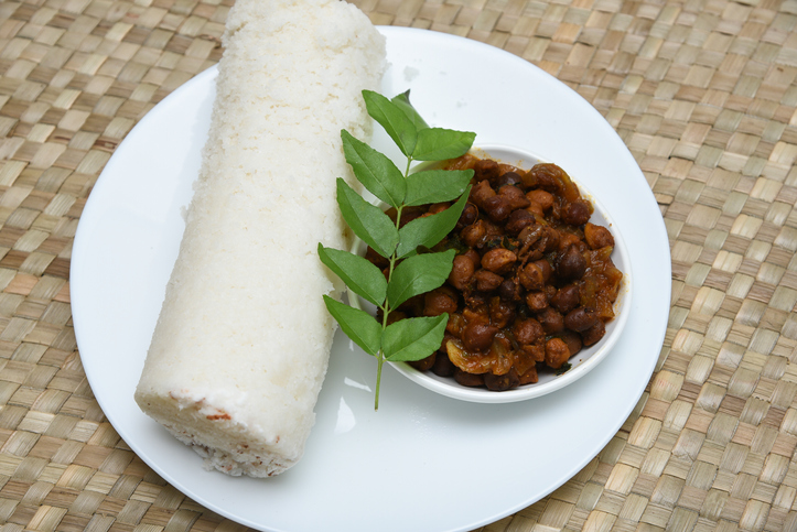 Popular South Indian breakfast puttu / pittu made of steamed rice flour and coconut in the bamboo mould with spicy beef or mutton meat curry , Kerala, India. Bamboo puttu. Sri lankan food