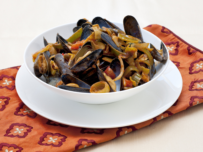 close up on a white bowl with sweet and sour boiled mussels and stir fried vegetables on table with napkin