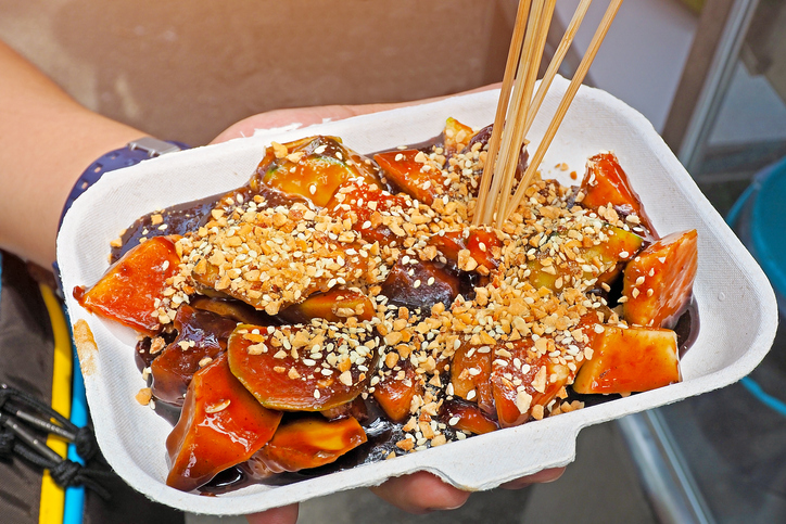 Asian local street food called Rojak is mixed of local tropical fruit topped with sweet and salt dip served on paper takeaway box tray buying from the street stall deck in Penang Malaysia