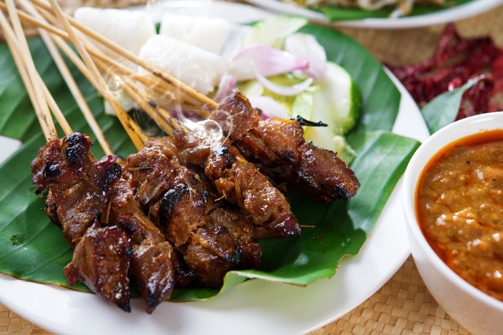 Satay or sate, skewered and grilled meat, served with peanut sauce, cucumber and ketupat. Traditional Malay food. Delicious hot and spicy Malaysian dish, Asian cuisine, Singaporean Cuisine