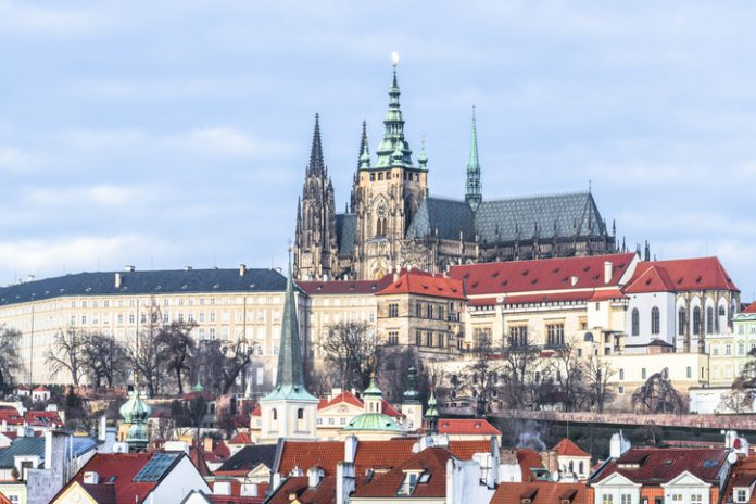The spires of the St. Vitus Cathedral among the picturesque tile roofs of the old quarter of Prague.