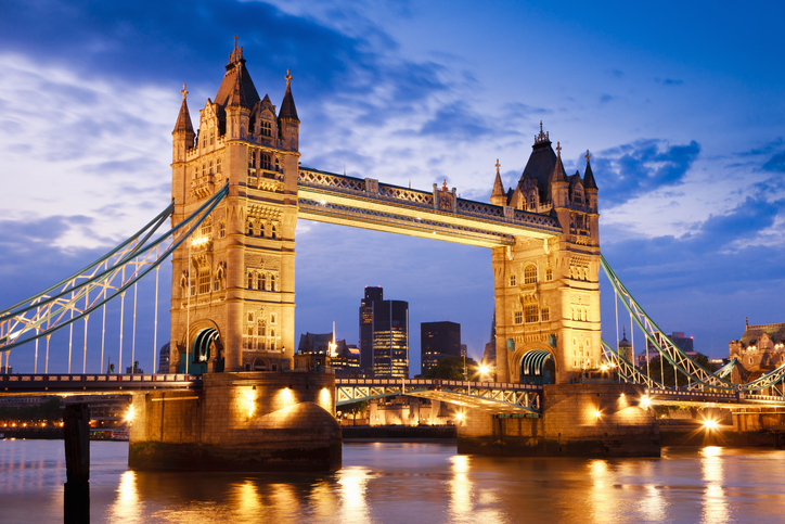 Tower Bridge in London, UK, at the beginning of night, brightly illuminated with reflections on the River Thames.