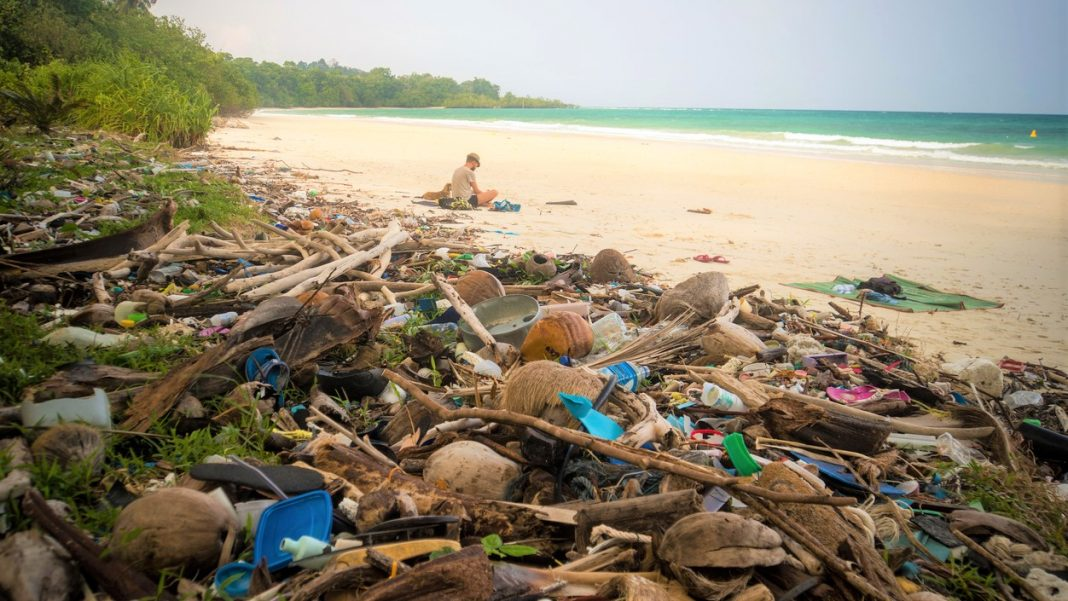 garbage on a beach left by tourist, environmental pollution concept picture. trash nailed by a wave from the sea on a beach. tourist resting on the beach near the big mountain of garbage, Overtourism