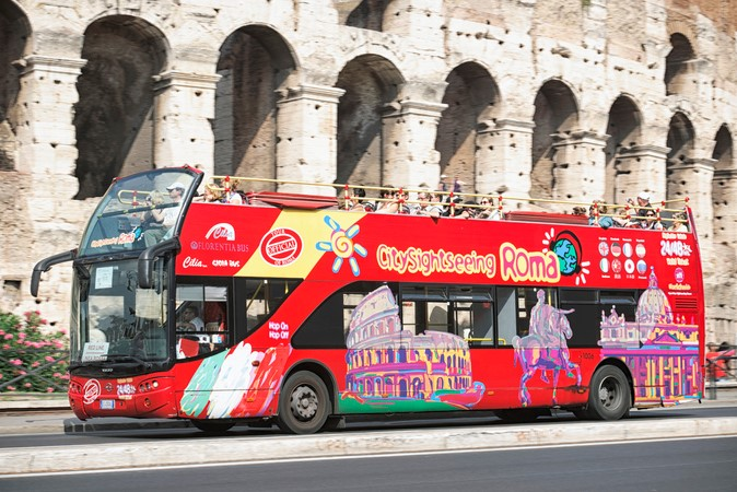 Rome, Italy - September 24, 2011: Tourists on an open-top tour bus operated by CitySightseeing as it passes the Colosseum in central Rome.