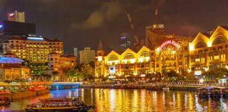 A traditional bumboat on the Singapore River at night, with Clarke Quay on the left and Riverside Point on the right.