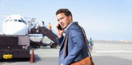 Young male professional hip businessman talking on smartphone boarding airplane going flying on business trip.a