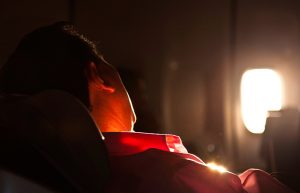 Business traveller sleeping while flying on a business trip.