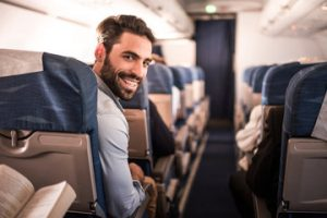 A happy business traveller sitting on a plane