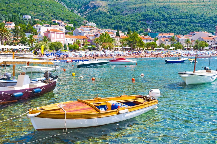 The small boats in moored harbor with the public beach on the background, Petrovac, Montenegro.