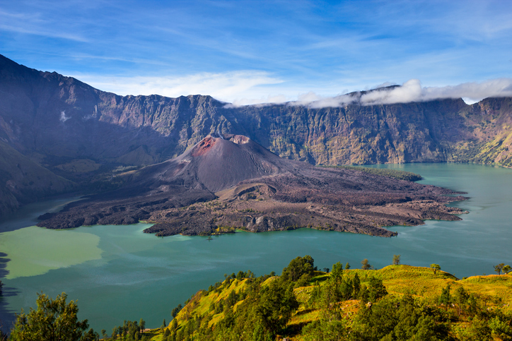 The caldera of Mount Rinjani with the crater lake Segara Anak and the volcanic cone Gunung Baru. Mount Rinjani is an active volcano and a popular hiking destination on the Island of Lombok, Indonesia.